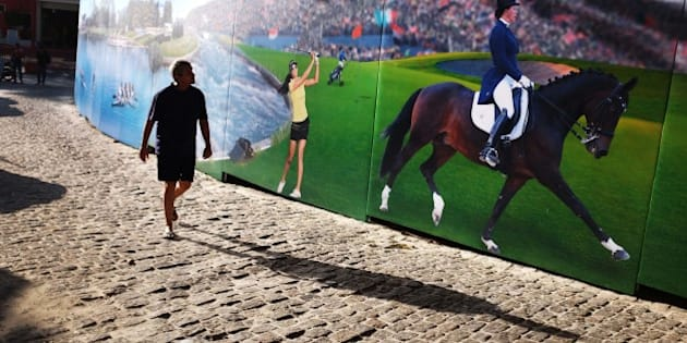 A pedestrian walks by a mural of Russian Olympic athletes on Copacabana beach Monday, Aug. 1, 2016, in Rio de Janeiro, Brazil. IOC President Thomas Bach defended the decision not to ban Russia's entire team from the Rio Games, declaring that the doping crisis won't damage the Olympic body's credibility and taking a swipe at global anti-doping officials for failing to act sooner against state-sponsored cheating in Russia. (AP Photo/David Goldman)