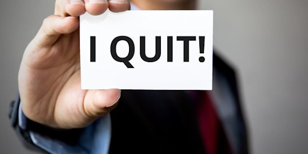 Businessman presenting 'I Quit' word on white card.