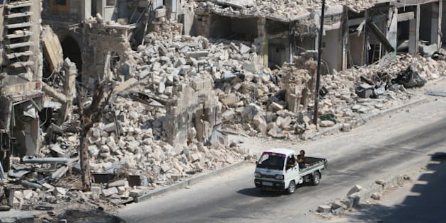 Men ride on a pick-up truck past damaged buildings in the rebel-held Bab al-Hadid neighbourhood of Aleppo, Syria August 18, 2016. REUTERS/Abdalrhman Ismail