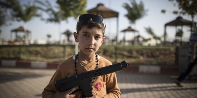 SANLIURFA, TURKEY - SEPTEMBER 24: A Syrian refugee boy poses with a toy gun at a tent city in the Akcakale District of Sanliurfa, Turkey on September 24, 2015. 260 thousand Syrians who have escaped war and found asylum in Turkey are now living in camps with opportunities that mean they don't miss what they've left behind. (Photo by Aykut Unlupinar/Anadolu Agency/Getty Images)