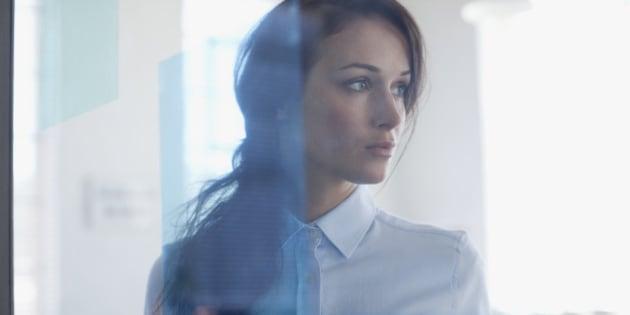 Pensive businesswoman in office window