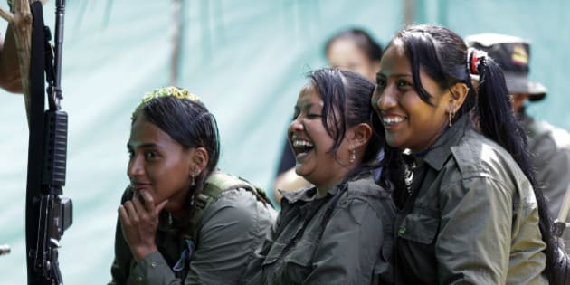 CORRECTS DATE PHOTO TAKEN - In this Aug. 16, 2016 photo, rebels of the 32nd Front of the Revolutionary Armed Forces of Colombia, or FARC, laugh during a break, at their camp in the southern jungles of Putumayo, Colombia. As Colombia's half-century conflict winds down, with the signing of a peace deal perhaps just days away, thousands of FARC rebels are emerging from their hideouts and preparing for a life without arms. (AP Photo/Fernando Vergara)