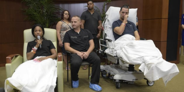 Shooting victim Angel Santiago, right, wipes away a tear as Patience Carter, of Philadelphia, left, relays her experience of being in the mass shooting at the Pulse nightclub during a news conference at Florida Hospital Orlando Tuesday, June 14, 2016, in Orlando, Fla. Listening at center is Dr. Brian Vickaryous.  (AP Photo/Phelan M. Ebenhack)