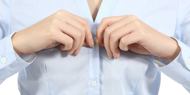 Closeup of a woman hands unbuttoning a shirt isolated on a white background