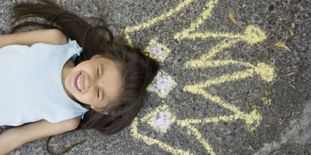 Enthusiastic girl with sidewalk chalk crown overhead