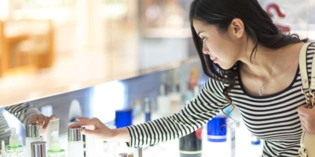 young woman choosing cosmetics in shopping mall