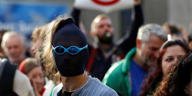 A masked demonstrator protests outside a congress centre where negotiators are expected to discuss the 14th Round of the Transatlantic Trade and Investment Partnership (TTIP) in Brussels, Belgium, July 12, 2016. REUTERS/Francois Lenoir