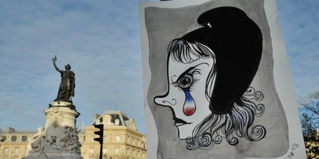 In this photo taken on Sunday Nov. 22, 2015  in Paris shows a drawing of a Marianne, symbol of the French Republic, crying and which hangs on the Place de la Republique. As Paris reeled from the worst attacks France has known since the end of World War II, its street artists took to city walls and billboards to paint notes of defiance.  (AP Photo/Binta Epelly)