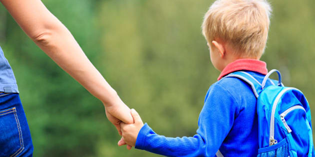 Mother holding hand of little son with backpack outdoors, back to school