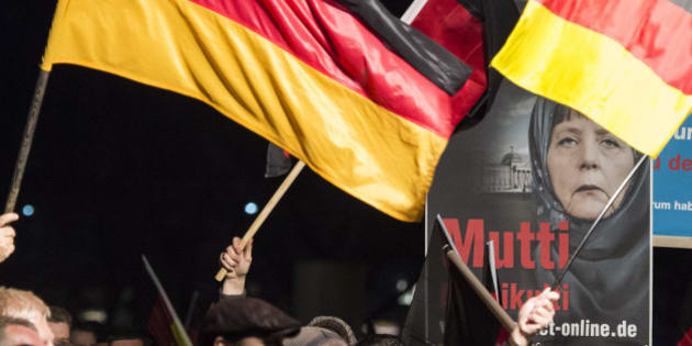 A banner reading 'Mum multiculti' and depicting a manipulated image German Chancellor Angela Merkel is carried by a protester behind the German flag as some thousands of people take part in a demonstration initiated by the Alternative for Germany (AfD) party against what they call the uncontrolled immigration and asylum abuse in Erfurt, central Germany, Wednesday, Nov. 4, 2015. (AP Photo/Jens Meyer)