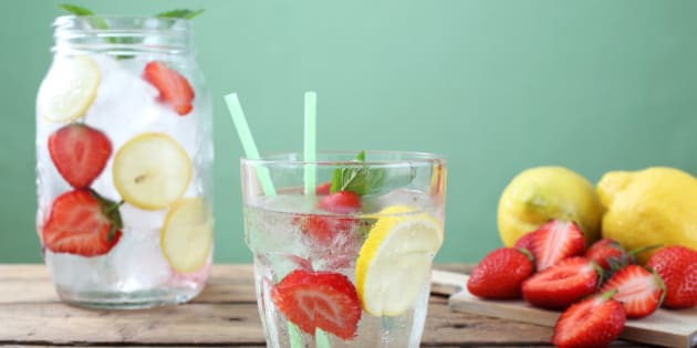 ice long drink strawberry and lemon in glass  green background