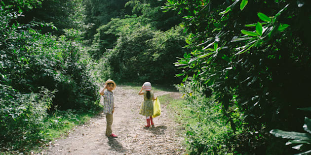 2 young friends walking down a forest track.