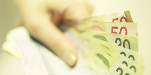 Hand holding Canadian money