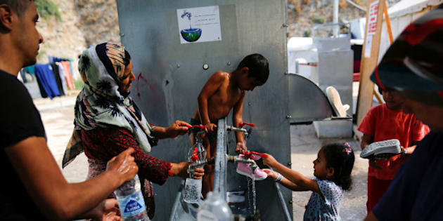 Anis, 4, from Syria (C) is bathed by his mother, as others wash their clothes and shoes, at the Souda municipality-run camp for refugees and migrants on the island of Chios, Greece, September 6, 2016. REUTERS/Alkis Konstantinidis