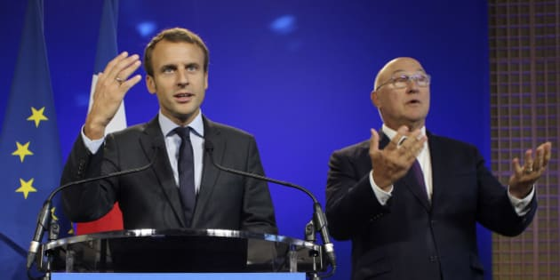 Outgoing Economy Minister Emmanuel Macron, left, and Finance Minister Michel Sapin gesture after the hand over ceremony at the Economy Ministry in Paris, Wednesday, Aug. 31, 2016. Macron says he's leaving his job as economy minister because he wants to take new risks, after a tenure marked by controversial labor reforms. (AP Photo/Thibault Camus)
