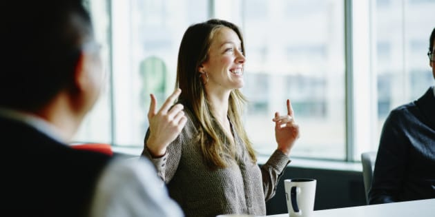 Smiling businesswoman leading project discussion during meeting with coworkers at office conference room table