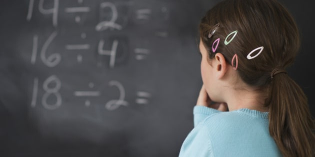 Girl looking at math equations on blackboard