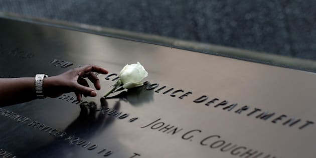 A woman places a single white rose at the edge of the South Pool of the 911 Memorial atop the area of the memorial for New York City Police (NYPD) officers killed in the 2001 attacks on the World Trade Center, following the deadly shootings of police officers in Dallas, Texas, in Manhattan, New York, U.S., July 8, 2016. REUTERS/Mike Segar TPX IMAGES OF THE DAY