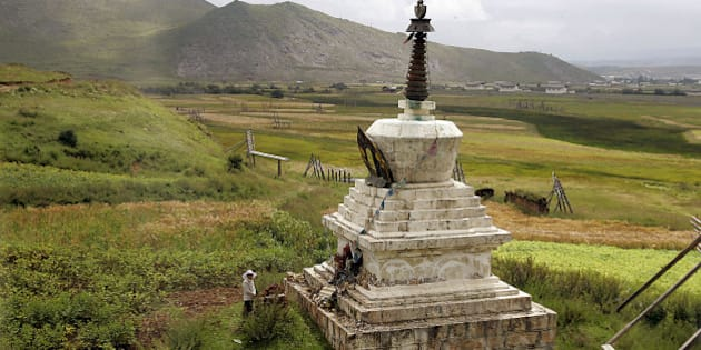 """A woman stands  in front of a Tibetan Buddhism ritual monument in Shangri La County, in northwestern Yunnan province  Saturday Aug. 26, 2006.  Shangri La village, is a popular tourist destination to visit the mythical land of """"Shangri-La"""" made famous in James Hilton's 1933 book """"Lost Horizon.""""  (AP Photo/ Eugene Hoshiko)"""