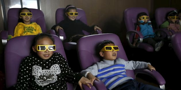 Children watch a 3D war movie at a community theatre in Hefei, Anhui province, March 29, 2015. Picture taken March 29, 2015. REUTERS/William Hong
