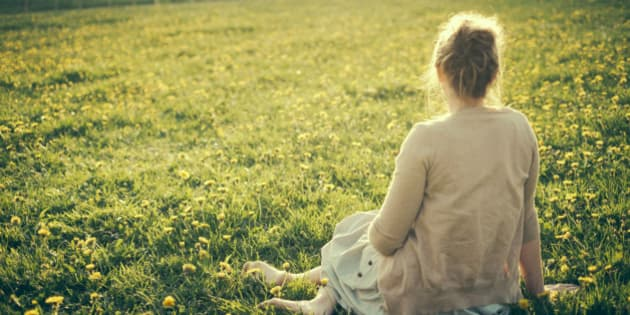 Young woman sitting in dandelion field in early spring in rural France.