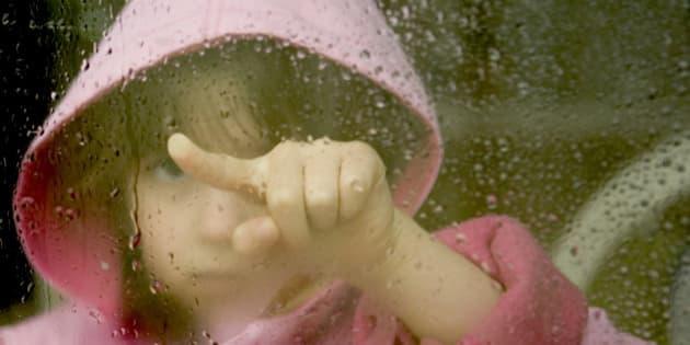Girl looking through a foggy wet window