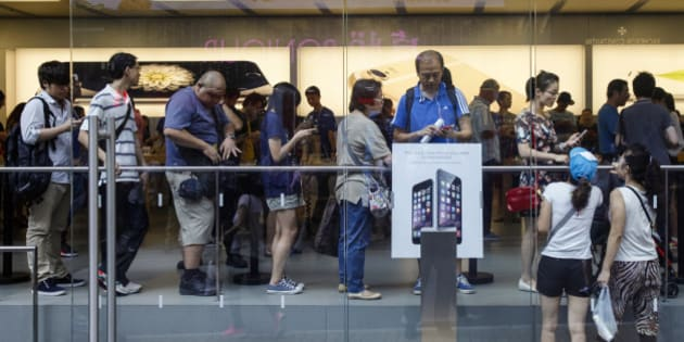 "People queue inside an Apple store to buy the new iPhone 6 and 6 Plus in Hong Kong October 9, 2014. The iPhone 6 will be sold in Mainland China from Oct 17, after rigorous regulator scrutiny led to Apple Inc reassuring the Chinese government that the smartphones did not have security ""backdoors"" through which U.S. agencies can access users' data. The iPhone 6 and 6 Plus were released on Sept 19 in the United States and elsewhere, but regulatory delay meant Chinese consumers had to wait. Picture taken October 9, 2014. REUTERS/Alex Lee (CHINA - Tags: SCIENCE TECHNOLOGY BUSINESS POLITICS)"