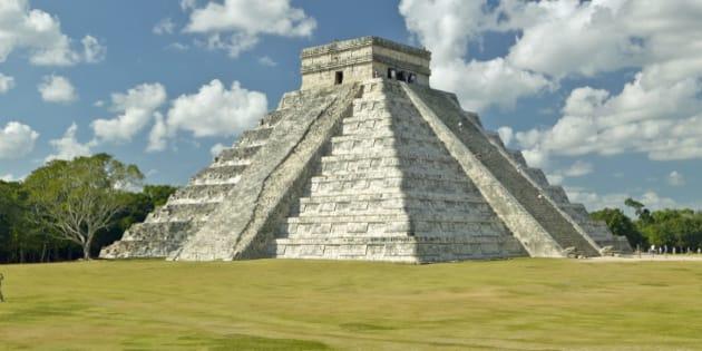 White puffy clouds over the Mayan Pyramid of Kukulkan (also known as El Castillo) and ruins at Chichen Itza, Yucatan Peninsula, Mexico