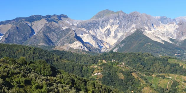 Panoramic view of the Alpi Apuane mountain chain with white marble quarries in Tuscany, Italy.