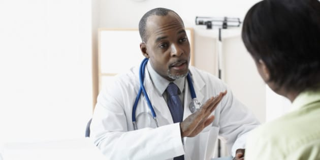 African male doctor talking to patient