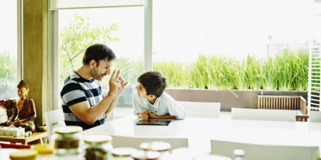 Smiling father and son in discussion while working on digital tablet at dining room table