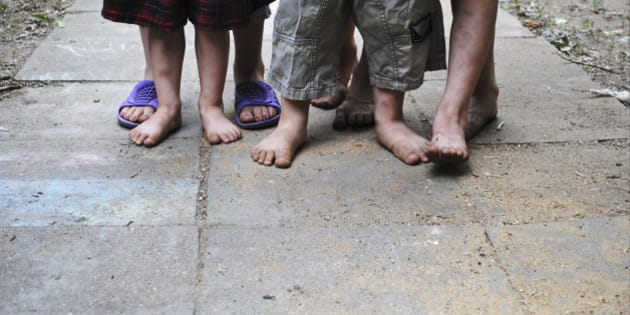 Homeless children with bare feet standing on a stone path.