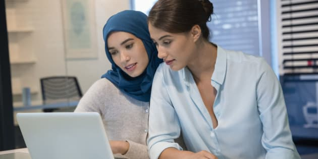 Two businesswomen looking at a laptop in an office