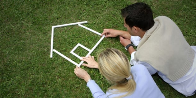 Young couple making house shape with rulers on grass