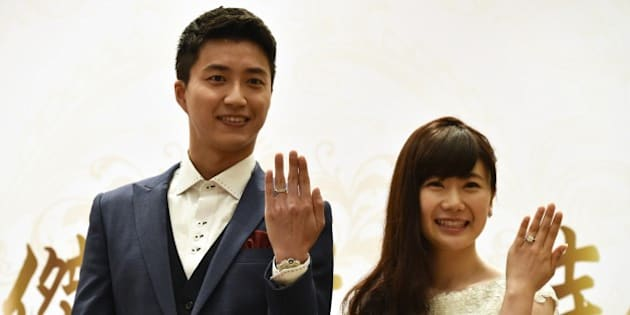 Taiwanese table tennis player Chiang Hung-chieh (L) and his Japanese wife Ai Fukuhara display their wedding rings during a press conference in Taipei on September 22, 2016. The couple made the announcement at a press conference saying they got married on September 1 in Tokyo. / AFP / SAM YEH        (Photo credit should read SAM YEH/AFP/Getty Images)