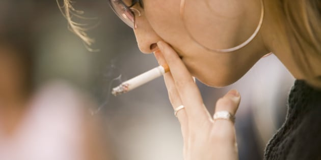 Young woman wearing sunglasses, smoking outdoors, close-up