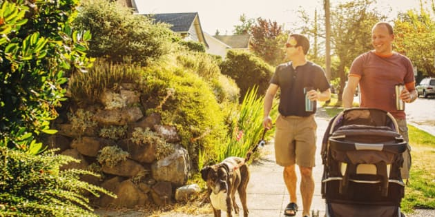 Caucasian gay couple walking dog and pushing stroller on sidewalk