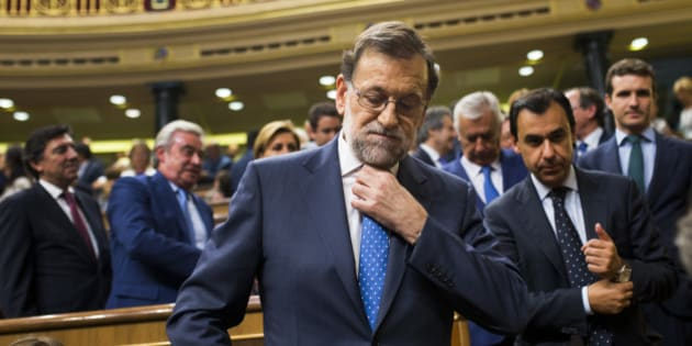 Spain's acting Prime Minister and Popular Party leader Mariano Rajoy adjusts his tie as he leaves at the end of the first of the two-day investiture debate at the Spanish parliament in Madrid, Tuesday, Aug. 30, 2016. Rajoy started a two-day parliamentary debate later Tuesday ahead of a vote on his bid to form a minority government and end an eight-month political impasse, but the signs are he won't be successful. (AP Photo/Francisco Seco)