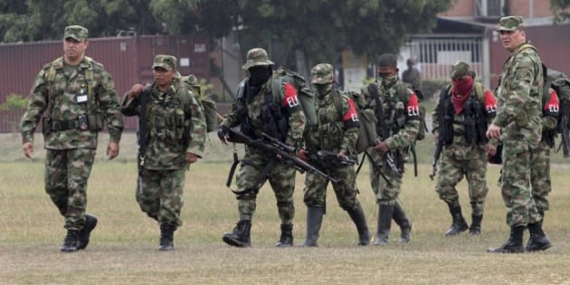 Soldiers, left and right, escort rebels of the National Liberation Army, ELN, who gave themselves up upon their arrival to a military base in Cali, Colombia, Tuesday, July 16, 2013. Thirty guerrillas of the country´s second largest rebel group surrendered Monday in a military post in the southern state of Cauca, President Juan Manuel Santos said. (AP Photo/Juan Bautista Diaz)