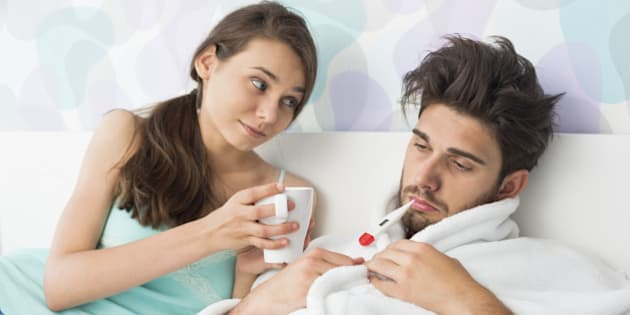 Young woman giving coffee mug to man with thermometer in mouth