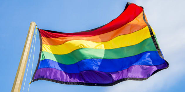 Gay rainbow flags waving over blue sky background