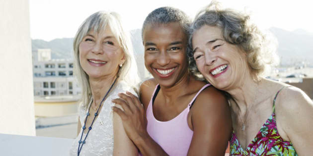 Women smiling together on urban rooftop