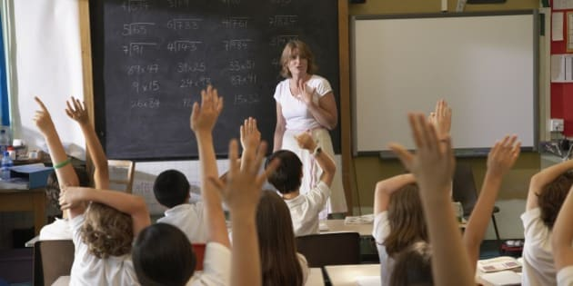 Multi-ethnic children with hands raised in class