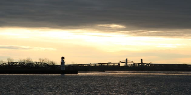 'Back lit lighthouse, and Mercier Bridge with morning traffic, a December morning.Lake Saint-Louis, or in French Lac Saint-Louis, is a lake in extreme southwestern Quebec, Canada, adjoining the Island of Montreal at the confluence of the Saint Lawrence and Ottawa Rivers. One can actually see a line in the middle of the lake where the two different-coloured waters meet.'