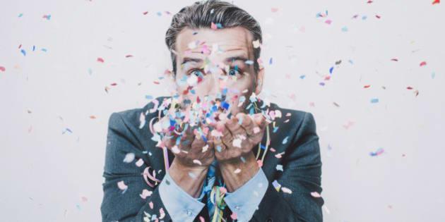 Business man blowing confetti facing camera, studio-portrait.