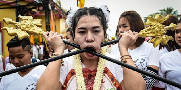 TOPSHOT - A devotee of the Nine Emperor Gods marches with large poles pierced through her cheeks during the annual Phuket Vegetarian Festival in the southern province of Phuket on October 1, 2016.  Swords, axe handles, kebab skewers and even a model boat were just some of the objects placed in devotees pierced cheeks as southern Thailands gruesome vegetarian festival got under way. / AFP / LILLIAN SUWANRUMPHA        (Photo credit should read LILLIAN SUWANRUMPHA/AFP/Getty Images)