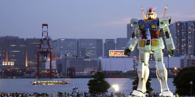 In this photo taken on July 11, 2009, people crowd to see 18-meter (60-foot) tall Gundam at a park in the manmade Odaiba island in Tokyo, Japan. If anything can encourage busy Tokyoites to take notice of their city's bid to host the 2016 Olympics, it's a replica of the popular robot animation Mobile Suit Gundam, the Japanese anime series robot, big enough to take on Godzilla. AP Photo/Koji Sasahara)