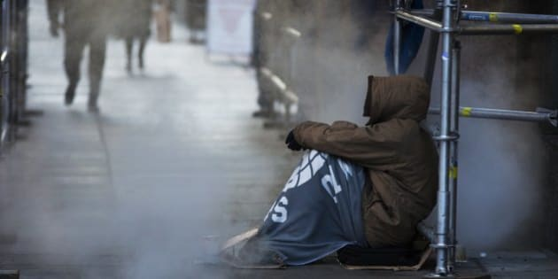TORONTO, ON - JANUARY 4: A homeless man tries to keep warm near a steam vent in the bone chilling winter temperatures of -13 in downtown Toronto, Ontario.        (Todd Korol/Toronto Star via Getty Images)