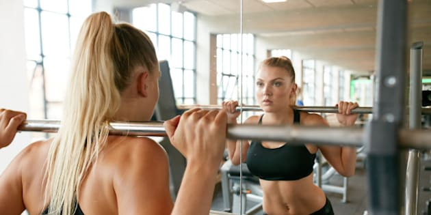 Muscular caucasian blond woman in a gym doing squats with a barbell on her shoulders while looking at mirror. Young woman working with weights at health club.