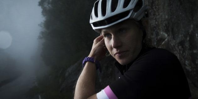 Female cyclist on mountain road, ajusting helmet